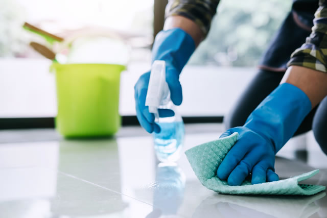 Husband housekeeping and cleaning concept, Happy young man in blue rubber gloves wiping dust using a spray and a duster while cleaning on floor at home