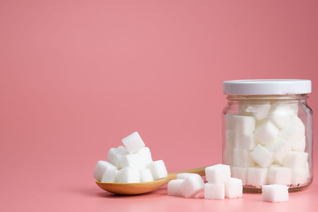 Cube granulated sugar in a glass jar and on wooden spoon for adding sweetness. some parts was poured on a pink background. - image