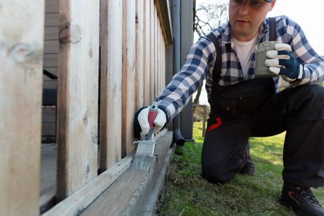 柵を塗装する男性