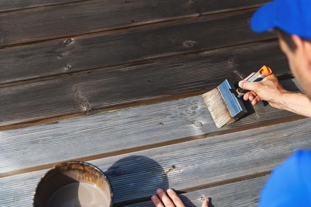 ウッドデッキを塗装する男性