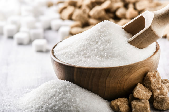 White sugar in wooden bowl with scoop on white table. White and brown sugar cubes in background.