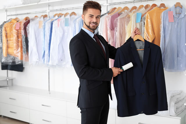 Young male worker removing dirt from clothes at dry-cleaner's