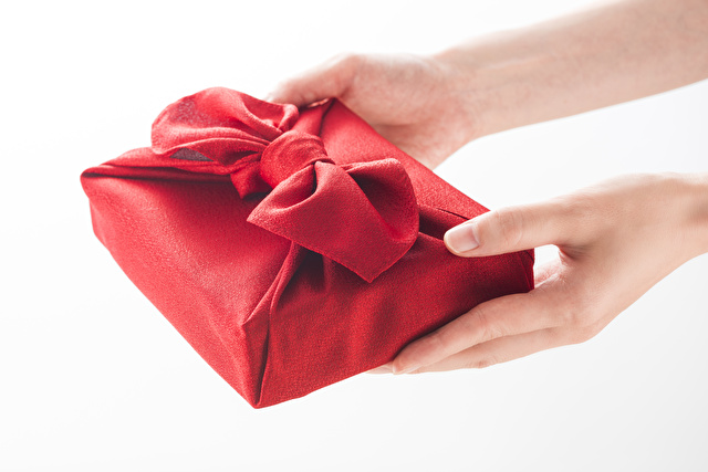 風呂敷包の手土産を渡す女性の手
