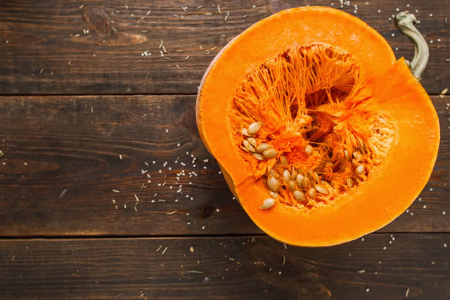Cut half of orange pumpkin on wood free space flat lay. Top view on rustic wooden table with cutaway fresh squash. Seasonal, dieting, vegetarian cuisine concept. Free space for your text.
