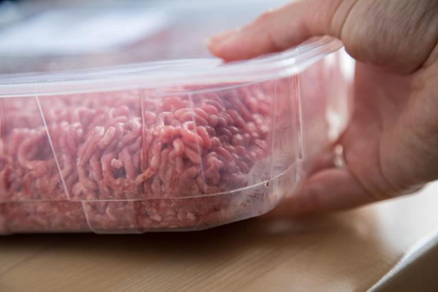 Weilbliche Hand nimmt verpacktes Hack aus Rind und Schwein