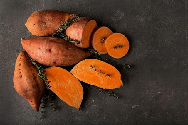 Raw sweet potato on grey table
