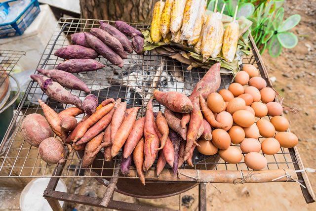 Sweet potato and egg grilled on stove in countryside store.Thailand