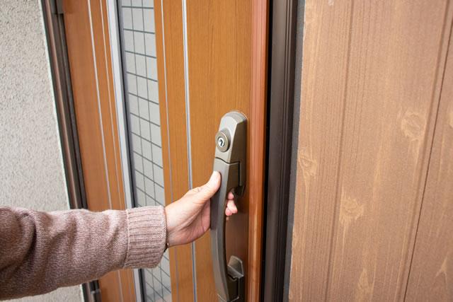 玄関のドアを持つ高齢者