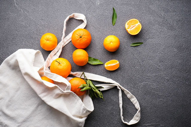Tangerines with green leaves on a dark background with an eco bag. Flat lay