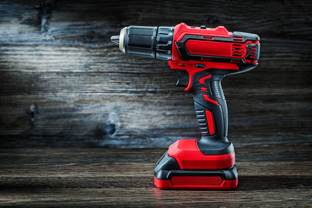 red cordless drill driver electric screwdriver on vintage wood background
