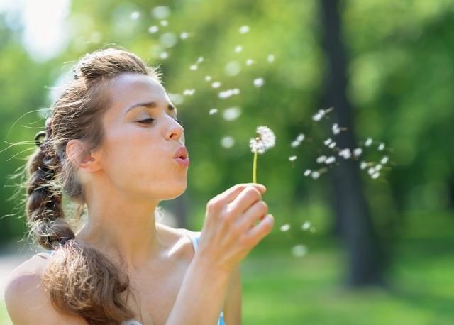 タンポポを吹き飛ばす若い女性