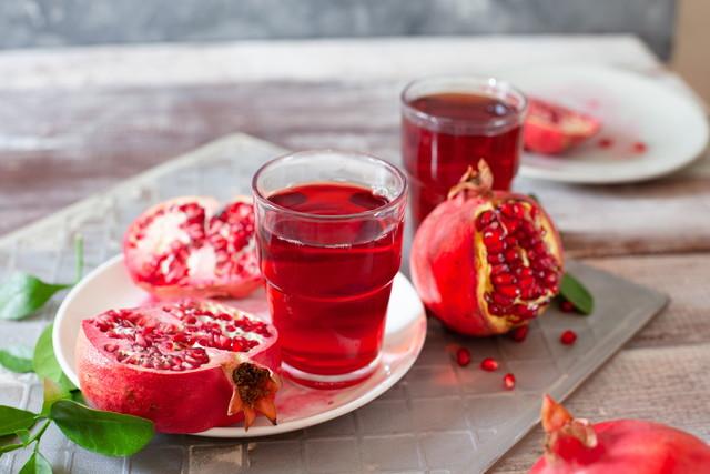木製のテーブルに新鮮なザクロの果実とザクロジュース