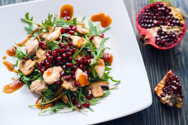 ザクロの種子と白い皿にルッコラの新鮮な健康的なチキンサラダ