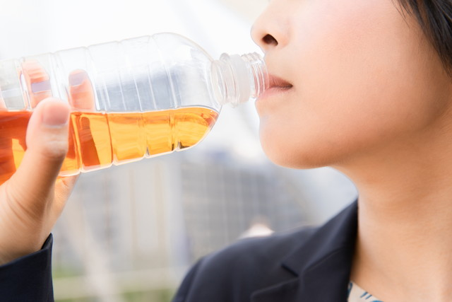 ペットボトルのお茶を飲む女性