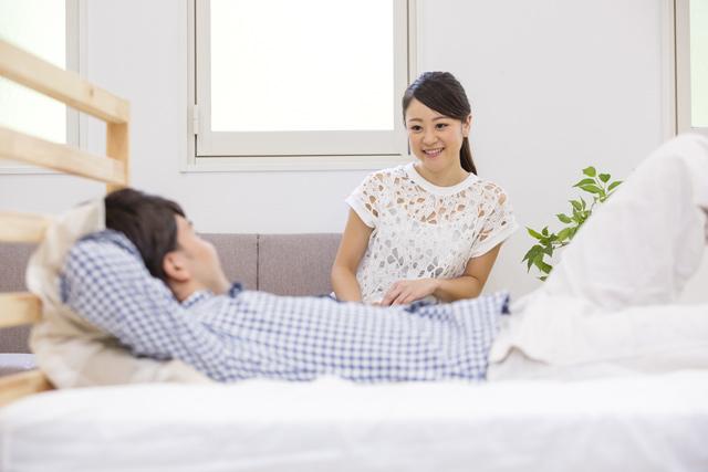 ベッドに寝る男性と座る女性