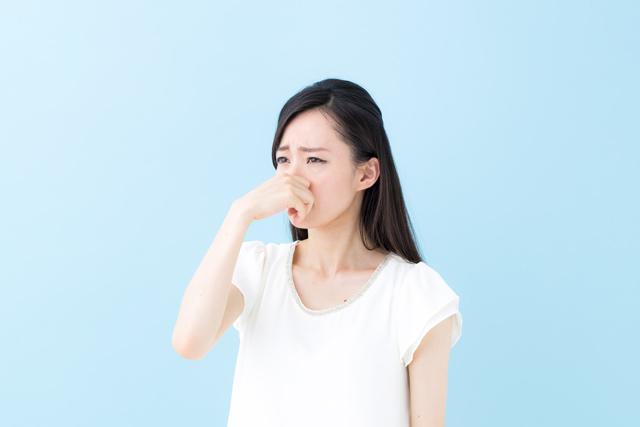 臭い 鼻をつまむ女性