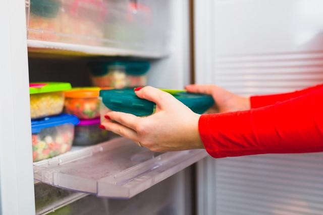 野菜の入った容器を冷蔵庫に入れる女性