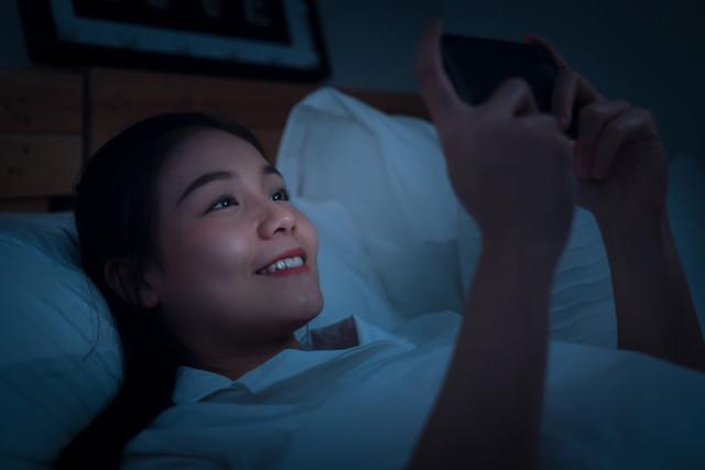 ベッドでスマホを使う女性