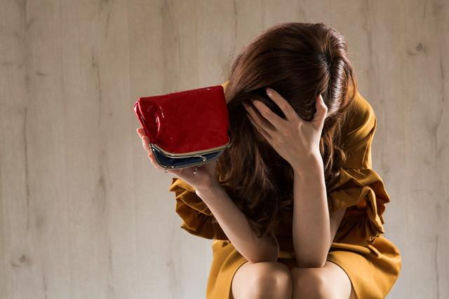 財布を持った落ち込む女性