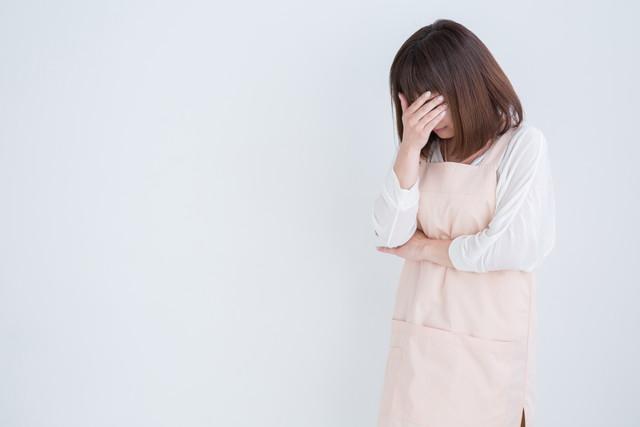 泣くエプロン姿の女性