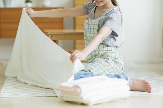 タオルをたたむ女性