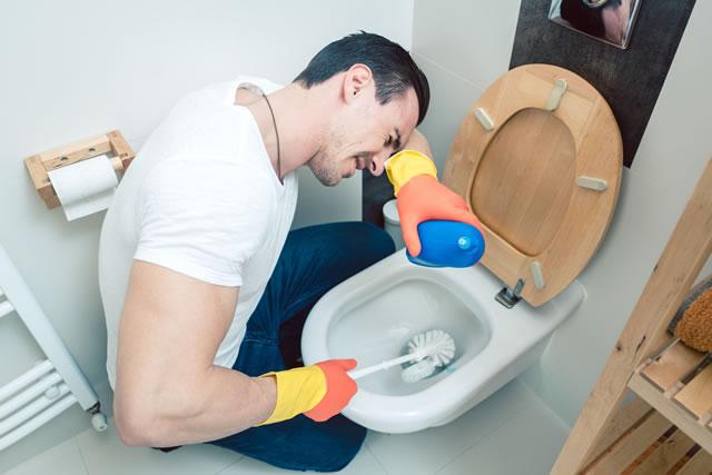 トイレ掃除をしている男性