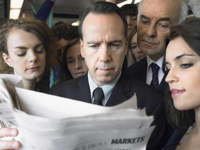 電車の中で新聞を読んで通勤者のグループのクローズアップ