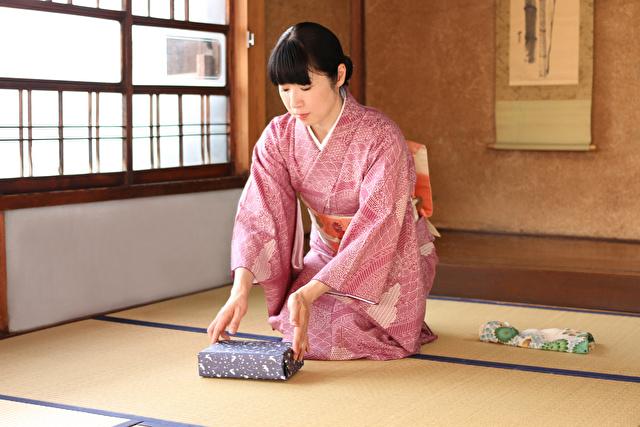 和室で手土産を差し出す着物姿の女性