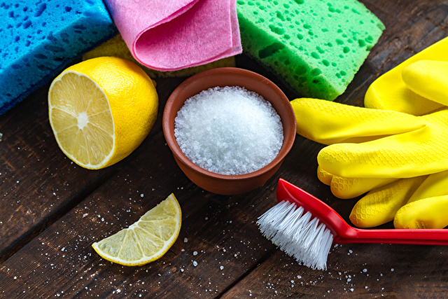 Lemon acid in a small plate, slice of lemon, a juicy lemon, sponge for washing dishes, brushes and yellow rubber gloves for cleaning the house on wooden background. Natural cleaning products