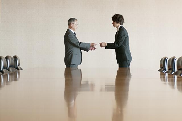 会議室で名刺交換をするビジネスマン