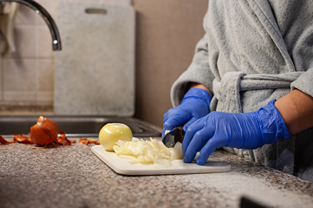 Slicing onions in the kitchen, close-up-hands of blue rubber gloves cut onions on the kitchen board. Healthy food, natural, vegetarian products.