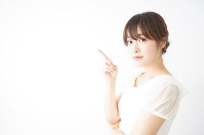 笑顔でポイントを示す若い日本人の女性