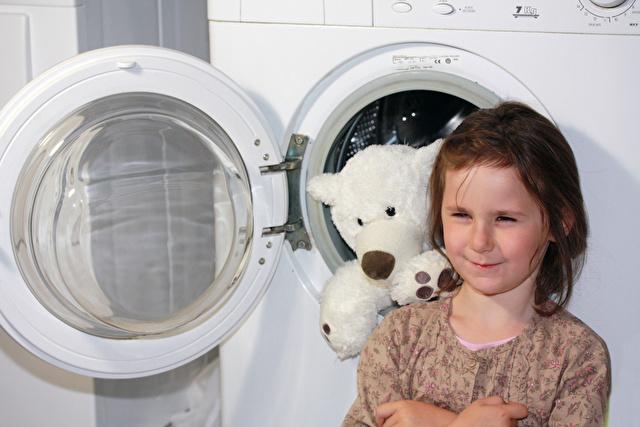 乾燥機とクマのぬいぐるみと少女
