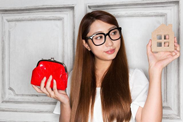 財布と家を持つ女性