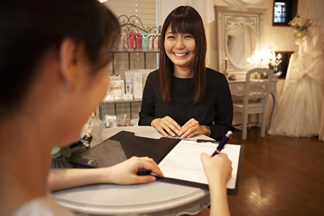 サロンで契約書を交わす笑顔のウエディングプランナーと新婦
