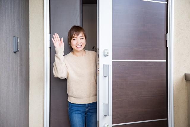 玄関で手を挙げる女性