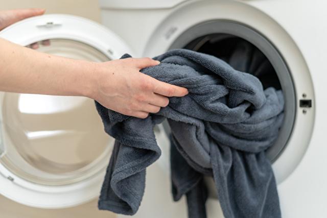 洗濯機から毛布を取り出す