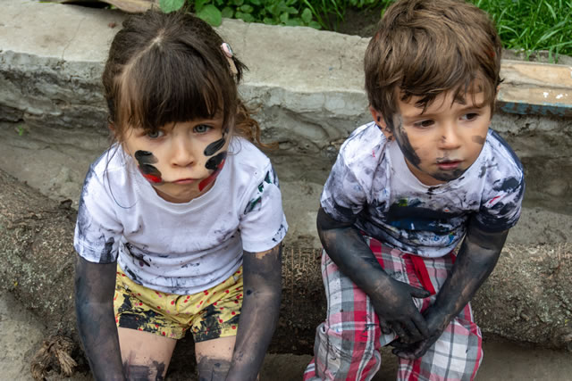 Children playing in mud, dirty cloth, messy face and hands in mud. Stains on clothes. Dirty cloth, washing laundry concept.