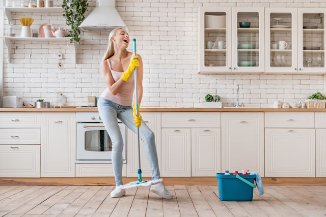 Happy woman cleaning home and having fun by singing at mop like in microphone