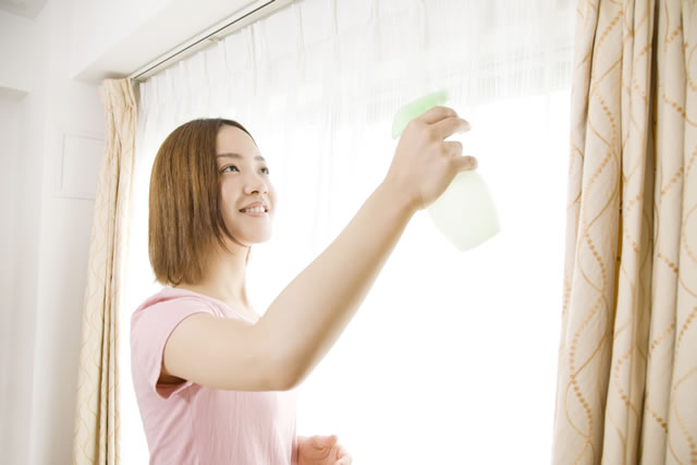 消臭スプレーをカーテンにかける女性