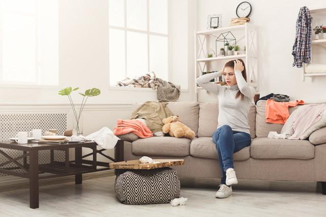 散らかった部屋のソファに座っている絶望的な女性