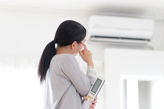 エアコンを見ながら悩む女性