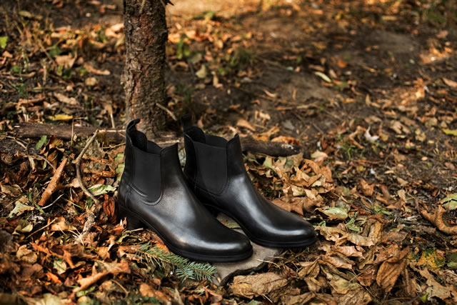 Black shiny leather women's chelsea boots on gray stone in a forest or park