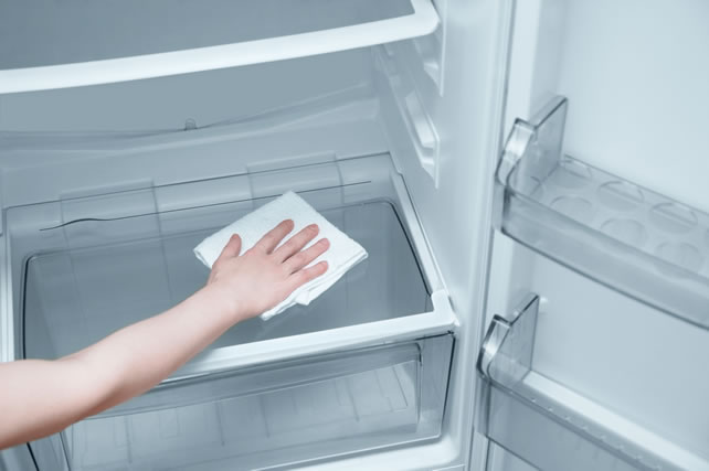 The girl's hand with a white rag washes the refrigerator