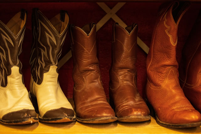 Three pairs of rugged leather cowboy boots on shelf