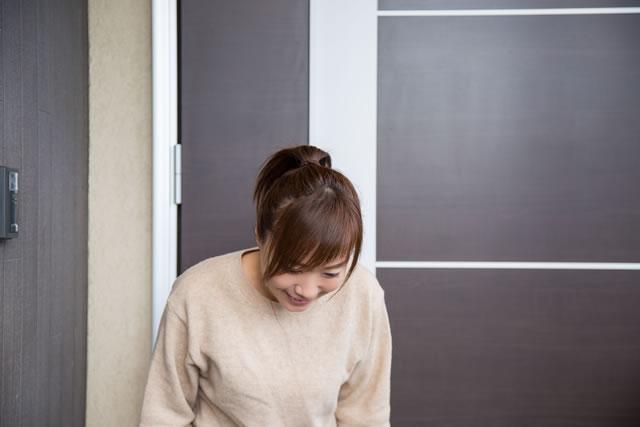 玄関で挨拶をする女性