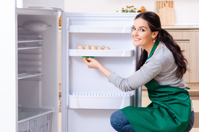 Young woman cleaning fridge in hygiene concept