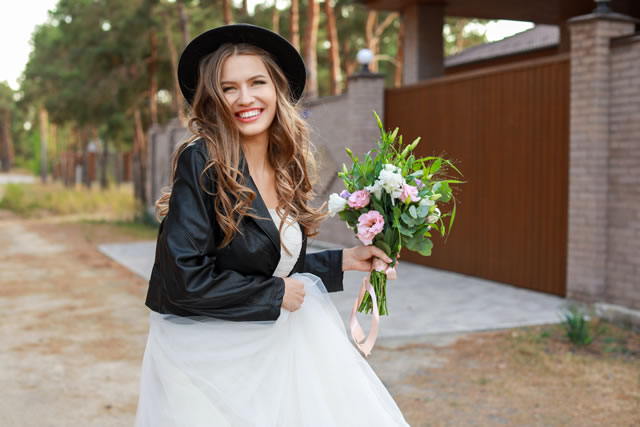 Beautiful young bride with bouquet of flowers on her wedding day outdoors