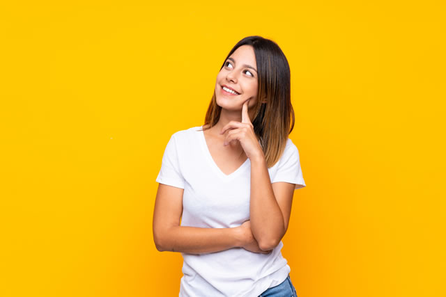 Young woman over isolated yellow background thinking an idea while looking up