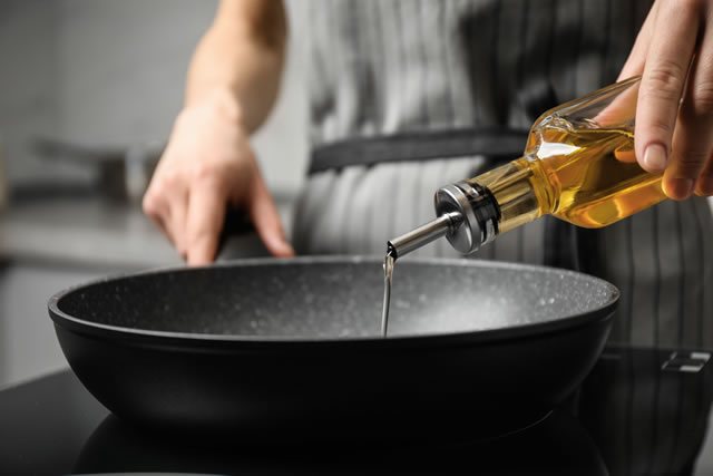 Woman pouring cooking oil from bottle into frying pan, closeup